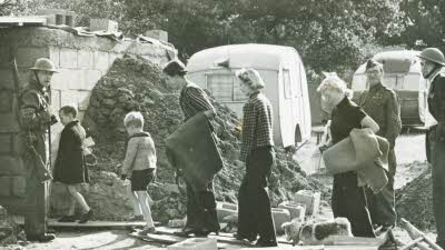 Citizens walk on duckboards past rubble with Home Guard soldiers looking on and caravans in the background