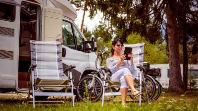 woman using a tablet outside her motorhome