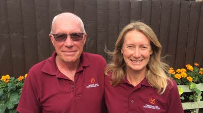 SIte managers Gary and Helen Harrison stand in front of flowers at Commons Wood Caravan and Motorhome Club Site in Hertfordshire