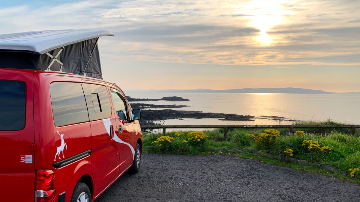 Red campervan overlooking sunset along the Causeway Coast Way