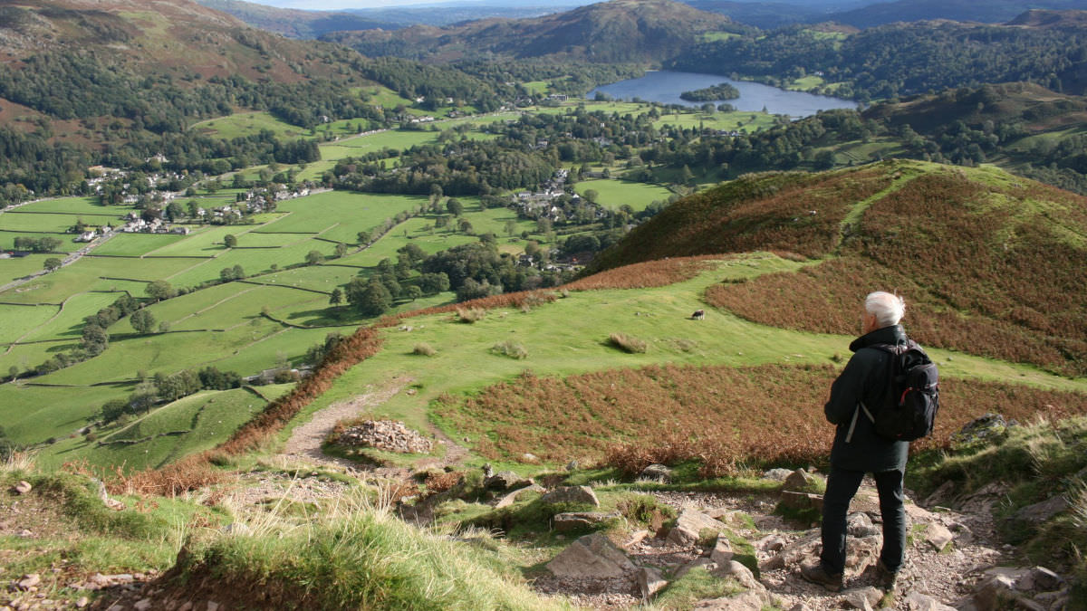 Walker overlooking grassy valley in the Lake District
