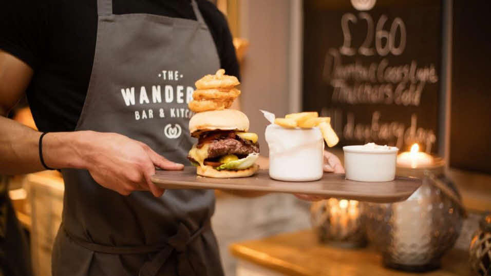 Man holding tray of burgers and chips at The Wanderer restaurant